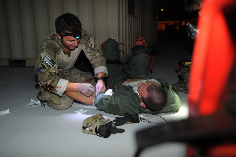 A U.S. Air Force Senior Airman from the 48th Rescue Squadron prepares to initiate an IV fluid resuscitation on a simulated patient during a mass casualty exercise at Davis-Monthan Air Force Base, Ariz., April 14, 2015.  For this exercise, several Airmen volunteered to play victims. This element added realism to the training, allowing the pararescuemen to work through the stress that each mission can bring. Due to security concerns, the last name is withheld. (U.S. Air Force photo by Senior Airman Betty R. Chevalier)