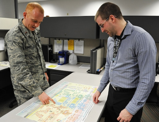 Second Lt. Matthew Ruden, acquisitions manager, Air Force Life Cycle Management Center, F-15 program, discusses acquisition flow with Bryan Gardner, systems engineer, AFLCMC, F-15 program. (Air Force photo by Michele Eaton)