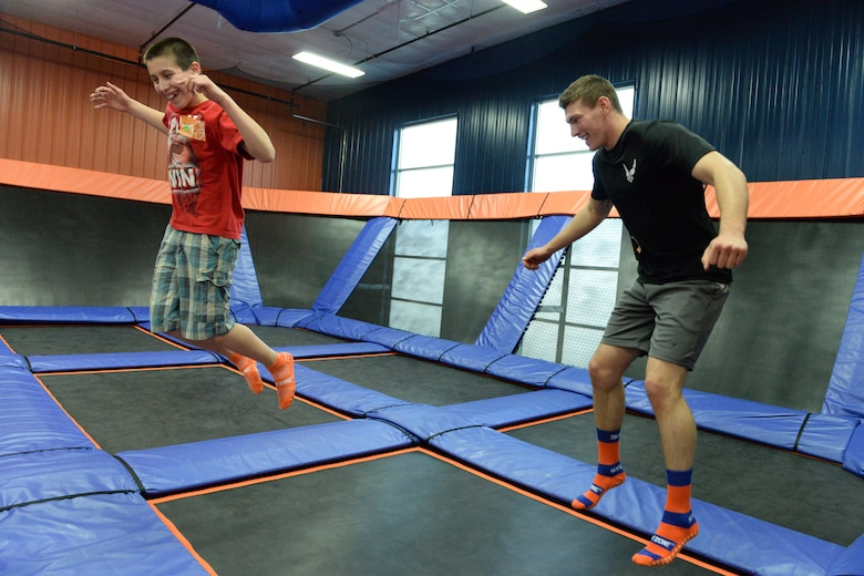 Senior Airman Sean Hummel, of the 119th Wing, right, jumps with his 'little wingman' Max during an outing at the Sky Zone indoor trampoline park, Fargo, North Dakota, April 16, 2015. Hummel has been mentoring Max for six years and is working on developing a youth mentoring program for members in the 119th Wing through the North Dakota Air National Guard Family Program called the Little Wingman Program. (U.S. Air National Guard photo by Senior Master Sgt. David H. Lipp/Released)