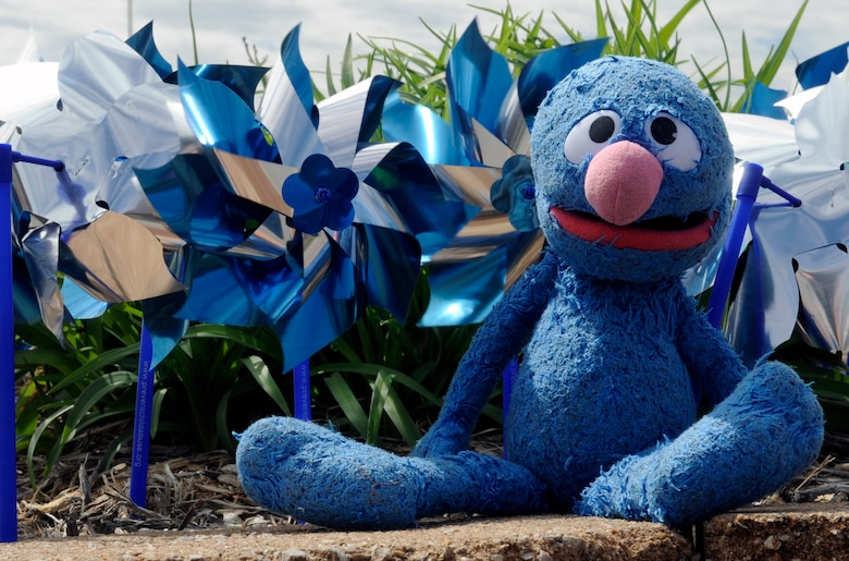 A stuffed animal of Grover from Sesame Street sits in front of blue and silver pinwheels at Whiteman air Force Base, Mo., April 14, 2015. Staff Sgt. Alexandra M. Longfellow, 509th Bomb Wing Public Affairs photojournalist, received Grover from a police officer on the night she was taken out of an abusive home.  April is Child Abuse Prevention Month and the pinwheel is a symbol for healthy starts for all children. (U.S. Air Force photo by Staff Sgt. Alexandra M. Longfellow/Released)