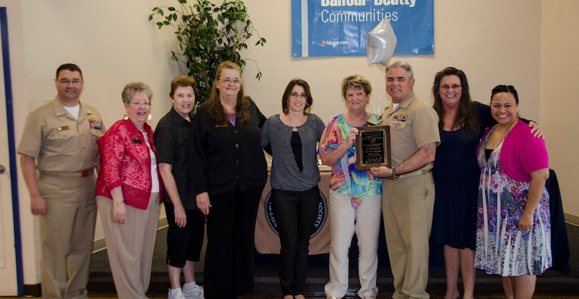 CAPT Timothy Sparks, Joint Base Charleston deputy commander, presents a volunteer appreciation award to the Navy Wives Club of America MenRiv Park #240, April 16, 2015 at Joint Base Charleston – Weapons Station, S.C. National Volunteer Week (April 12-18, 2015) is a program established by the Points of Light. Points of Light was founded in 1990 by President George H.W. Bush as an independent, nonpartisan, nonprofit organization to encourage and empower the spirit of service. (U.S. Air Force photo/Staff Sgt. AJ Hyatt)