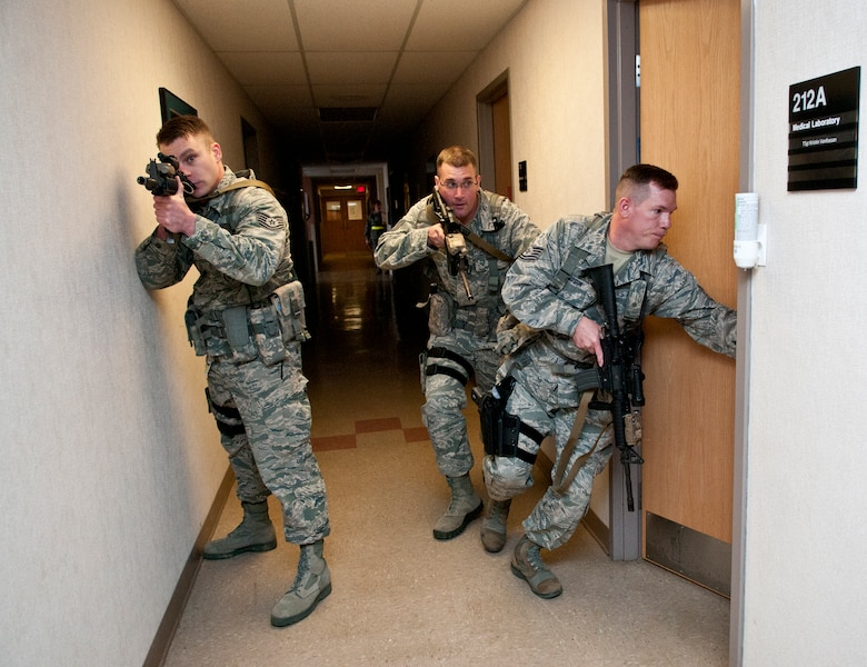 U.S. Air Force Tech. Sgt. Steve Thompson, Tech. Sgt. Gregory Oberfield and Tech. Sgt. Brandon Ostrowsky, with the 121st Security Forces Squadron, perform close quarter search and clear maneuvers in response to a simulated active shooter during a training exercise April 15, 2015 at Rickenbacker Air National Guard Base, Ohio. The training exercise was held to test the reactions of military members and the response time of security forces personnel. (U.S. Air National Guard photo by Tech. Sgt. Zachary Wintgens/Released)