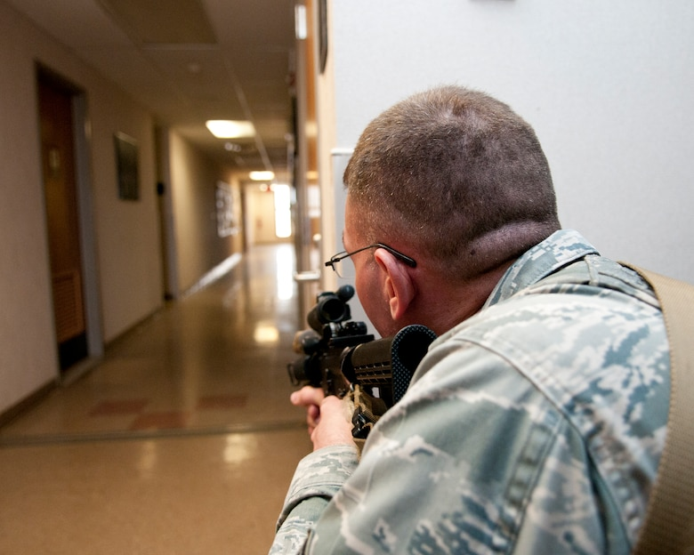 U.S. Air Force Tech. Sgt. Gregory Oberfield, with the 121st Security Forces Squadron, provides cover in response to a simulated active shooter training exercise April 15, 2015 at Rickenbacker Air National Guard Base, Ohio. The training exercise was held to test the reactions of military members and the response time of security forces personnel. (U.S. Air National Guard photo by Tech. Sgt. Zachary Wintgens/Released)