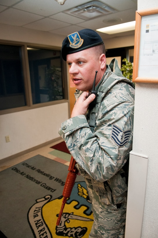 U.S. Air Force Tech. Sgt. Patrick Linder, with the 121st Security Forces Squadron, utilizes radio communications during an active shooter training exercise April 15, 2015 at Rickenbacker Air National Guard Base, Ohio. The training exercise was held to test the reactions of military members and the response time of security forces personnel. (U.S. Air National Guard photo by Tech. Sgt. Zachary Wintgens/Released)