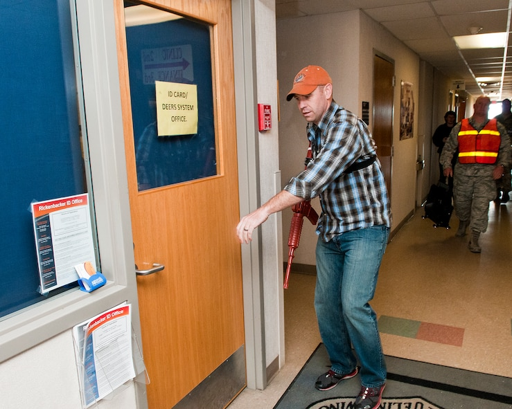 U.S. Air Force Senior Master Sgt. Richard Gay, superintendent with the 121st Inspector General's Office, attempts to gain access to rooms during a simulated active shooter exercise April 15, 2015 at Rickenbacker Air National Guard Base, Ohio. The training exercise was held to test the reaction of military members and the response time of security forces personnel. (U.S. Air National Guard photo by Tech. Sgt. Zachary Wintgens/Released)