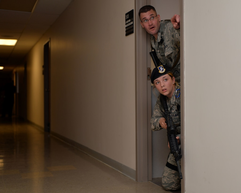 U.S. Air Force Tech. Sgt. Gregory Oberfield and Airman 1st Class Celina Huffman, with the 121st Security Forces Squadron, use cover to secure a building during an active shooter training exercise April 15, 2015 at Rickenbacker Air National Guard Base, Ohio. The training exercise was held to test the reaction of military members and the response time of security forces. (U.S. Air National Guard photo by Airman Ashley Williams/Released)