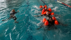 Trainees participate in an exercise during a survival, evasion, resistance and escape water survival course April 13, 2015, at Ramstein Air Base, Germany.  The one-day course provided Airmen from various career specialties training on how to properly react to an emergency situation in the water.  (U.S. Air Force photo/Senior Airman Nicole Sikorski)