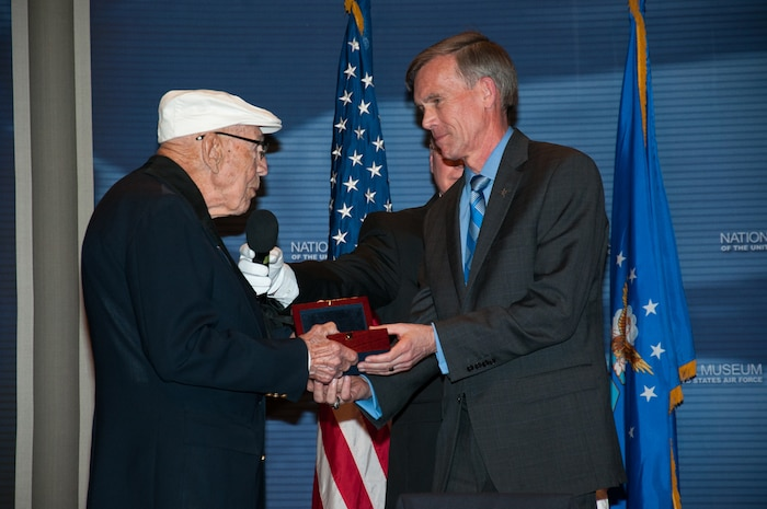 Doolittle Raider Lt. Col. Richard Cole presents the Raiders' Congressional Gold Medal to Museum Director Lt. Gen. (Ret.) John Hudson. The medal is on display in the museum's World War II Gallery in the Doolittle Raid exhibit. (U.S. Air Force photo by Niki Jahns)