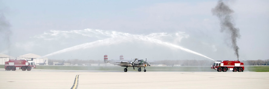"B-25 ""Panchito,"" owned by Larry Kelley and Lorie Thomsen, arrives at Wright-Patterson AFB following a ceremonial flight with the Doolittle Raiders Congressional Gold Medal on board. The aircraft was welcomed with a water arch by the Wright-Patterson AFB Fire Department. (U.S. Air Force photo by Will Haas)"