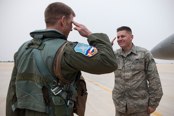 Senior Airman Mitchell Jamison, 120th Expeditionary Aircraft Maintenance Unit crew chief, salutes his father, Lt. Col. James Reeman, 120th Expeditionary Fighter Squadron F-16 Fighting Falcon pilot, April 16, 2015, at Kunsan Air Base, Republic of Korea. Reeman and Jamison, both from the 140th Wing, Colorado Air National Guard, are temporarily assigned to the Wolf Pack as part of a rotational Theater Security Package for approximately three months. (U.S. Air Force photo by Senior Airman Katrina Heikkinen/Released)