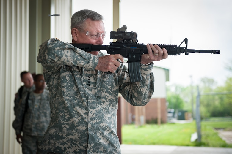 Army Gen. Frank J. Grass, chief of the National Guard Bureau, fires an M-4 rifle loaded with paint ball simunitions during a mission brief on the 123rd Special Tactics Squadron at the Kentucky Air National Guard Base in Louisville, Ky., April 18, 2015. The 123rd is the only special tactics unit in the Air National Guard with both combat controllers and pararescuemen. (U.S. Air National Guard photo by Maj. Dale Greer)