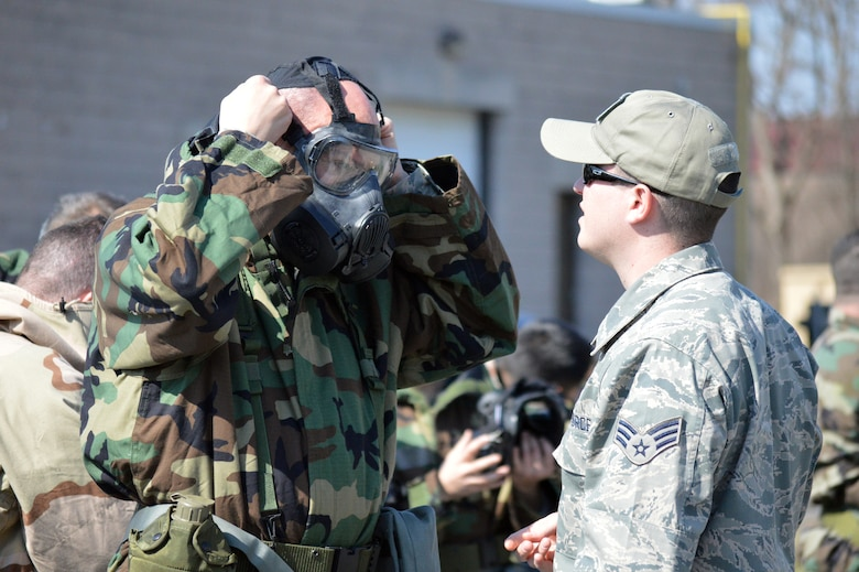 Senior Airman Patrick Irwin, 109th Civil Engineer Squadron's emergency management instructor, assists Lt. Col. Ronald Ankabrandt, 109th Airlift Wing inspector general, adjust his mask during the hands-on chemical, biological, radiological and nuclear training at Stratton Air National Guard Base, New York, on April 18, 2015. The training was part of the 109th AW's first ancillary training rodeo where more than 200 Airmen were trained on CBRN as well as self-aid and buddy care. (U.S. Air National Guard photo by Tech. Sgt. Catharine Schmidt/Released)