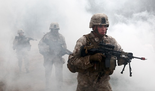 U.S. Marines with Fox Company, Battalion Landing Team 2/6, 26th Marine Expeditionary Force, use a smoke grenade to screen their movement as they prepare to enter a building during military operations in urban terrain (MOUT) training at Fort Pickett, Va., April 11, 2015. The 26th MEU is conducting realistic urban training in preparation for deployment in the 5th and 6th Fleet areas of responsibility later this year. (U.S. Marine Corps Photo by Staff Sgt. Bobby J. Yarbrough/Released)