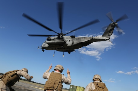 U.S. Marines with Combat Logistics Battalion 26, 26th Marine Expeditionary Unit (MEU), signal a CH-53E Super Stallion with Marine Medium Tiltrotor Squadron (VMM) 162 (Reinforced), 26th MEU, during helicopter support training at Fort Pickett, Va., April 11, 2015. The long distance transportation of supplies by air can be used to support troops ashore such as when conducting a humanitarian assistance or disaster relief mission where supplies are needed in a timely manner. The 26th MEU is conducting realistic urban training in preparation for deployment in the 5th and 6th fleet area of responsibility later this year. (U.S. Marine Corps Photo by Cpl. Jeraco Jenkins/ 26th Marine Expeditionary Unit Combat Camera/Released)