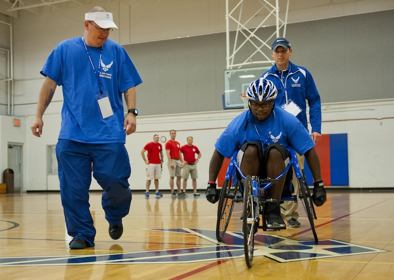Tech. Sgt. Ryan Delaney, an Air Force wounded warrior mentor, watches Tremayne Maxwell, an Air Force wounded warrior athlete, perfect his wheelchair basketball rolling skills during the first day of an introductory adaptive sports and rehabilitation camp at Eglin Air Force Base, Fla., April 13, 2015. Delaney, a flight chief with the 412th Security Forces Squadron at Edwards AFB, Calif., helped prepare approximately 45 participants in the week-long camp and training events. (U.S. Air Force photo/Samuel King Jr.)