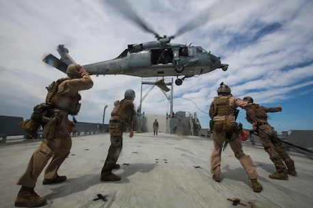 U.S. Marines and Sailors assigned to Force Reconnaissance Platoon, Maritime Raid Force, 26th Marine Expeditionary Unit (MEU) help lift a simulated casualty onto a SH-60 Seahawk during Visit, Board, Search, and Seizure (VBSS) training at Joint Base Langley-Eustis, Va., April 16, 2015. The Marines were evaluated on their training as part of preparation for deployment to the 5th and 6th Fleet Areas of responsibility later this year. (U.S. Marine Corps photo by Lance Cpl. Andre Dakis/26th MEU Combat Camera/Released)