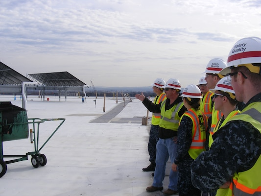Jeff McMaster explains to Naval Academy midshipment why the solar panels and the white painted rooftop contribute to the LEED-Silver design for the USAMRIID replacement project.