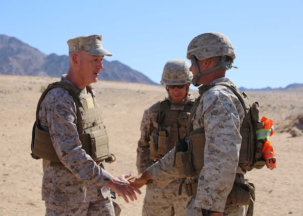 Commandant of the Marine Corps Gen. Joseph F. Dunford Jr., left, greets Capt. Joshua A. Loch, right, executive officer, and 1st Lt. Jonathon Yenny, center, platoon commander, both with Company A, Ground Combat Element Integrated Task Force, during a visit to Range 107, Marine Corps Air Ground Combat Center Twentynine Palms, California, April 18, 2015. From October 2014 to July 2015, the GCEITF will conduct individual and collective level skills training in designated ground combat arms occupational specialties in order to facilitate the standards-based assessment of the physical performance of Marines in a simulated operating environment performing specific ground combat arms tasks. (U.S. Marine Corps photo by Cpl. Paul S. Martinez/Released)