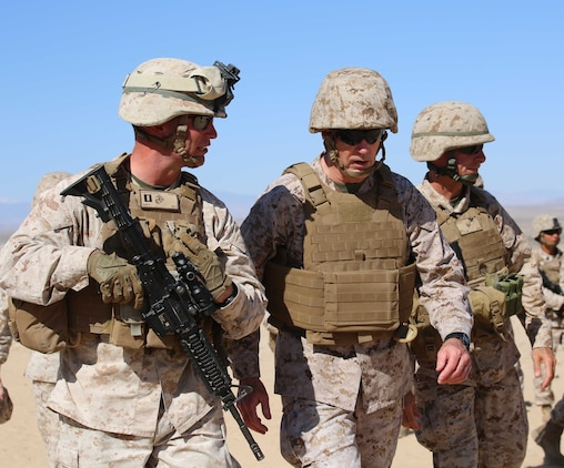 Commandant of the Marine Corps Gen. Joseph F. Dunford Jr., center, walks alongside Col. Matthew G. St. Clair, right, commanding officer, Ground Combat Element Integrated Task Force; and Capt. Raymond P. Kaster, left, company commander, Company A, GCEITF, during a visit to Range 107, Marine Corps Air Ground Combat Center Twentynine Palms, California, April 18, 2015. From October 2014 to July 2015, the GCEITF will conduct individual and collective level skills training in designated ground combat arms occupational specialties in order to facilitate the standards-based assessment of the physical performance of Marines in a simulated operating environment performing specific ground combat arms tasks. (U.S. Marine Corps photo by Cpl. Paul S. Martinez/Released)