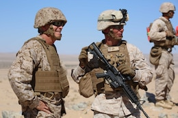 Brig. Gen. George W. Smith Jr., left, commanding general, Marine Corps Force Innovation Office, speaks with Capt. Raymond P. Kaster, right, company commander, Company A, during a visit to Range 107, Marine Corps Air Ground Combat Center Twentynine Palms, California, April 18, 2015. From October 2014 to July 2015, the GCEITF will conduct individual and collective level skills training in designated ground combat arms occupational specialties in order to facilitate the standards-based assessment of the physical performance of Marines in a simulated operating environment performing specific ground combat arms tasks. (U.S. Marine Corps photo by Cpl. Paul S. Martinez/Released)