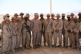 Commandant of the Marine Corps Gen. Joseph F. Dunford Jr, center, stands alongside Marines with the Ground Combat Element Integrated Task Force during a visit to Range 107, Marine Corps Air Ground Combat Center Twentynine Palms, California, April 18, 2015. From October 2014 to July 2015, the GCEITF will conduct individual and collective level skills training in designated ground combat arms occupational specialties in order to facilitate the standards-based assessment of the physical performance of Marines in a simulated operating environment performing specific ground combat arms tasks. (U.S. Marine Corps photo by Cpl. Paul S. Martinez/Released)