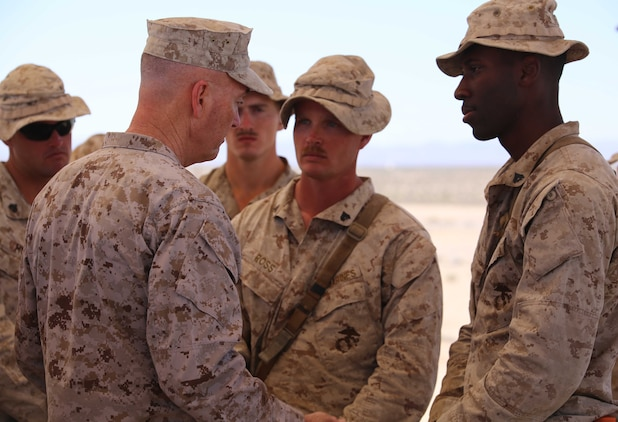 Commandant of the Marine Corps Gen. Joseph F. Dunford Jr., left, speaks with Corporals William L. Ross and Giovanni D. Destin, both riflemen with Company A, Ground Combat Element Integrated Task Force, during a visit to Range 107, Marine Corps Air Ground Combat Center Twentynine Palms, California, April 18, 2015. From October 2014 to July 2015, the GCEITF will conduct individual and collective level skills training in designated ground combat arms occupational specialties in order to facilitate the standards-based assessment of the physical performance of Marines in a simulated operating environment performing specific ground combat arms tasks. (U.S. Marine Corps photo by Cpl. Paul S. Martinez/Released)