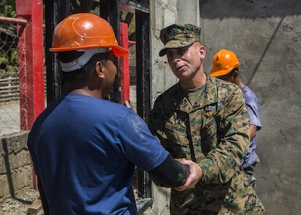 U.S. Marine Brig. Gen. Joaquin Malavet, right, I Marine Expeditionary Brigade commander, shakes the hand of Philippine Navy Petty Officer 3rd Class Alvin P Bautista, left, a Naval Combat Engineer Brigade engineer, at ENCAP Site 3, San Rafael Elementary School, Philippines, during exercise Balikatan 2015, April 17. Armed Forces of the Philippines Brig. Gen. Guillermo Molina  and Malavet visited the sites to meet the engineers who have been working shoulder to shoulder as well as get a firsthand look at the classrooms being built.