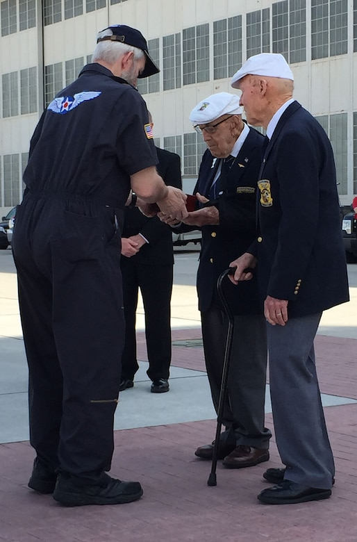 "Brian Anderson, Doolittle Tokyo Raiders Association sergeant of arms, hands the Congressional Gold Medal to Doolittle Raiders retired Lt. Col. Dick Cole and former Staff Sgt. David Thatcher after a ceremonial flight on board the B-25 ""Panchito"" at Wright-Patterson Air Force Base, Ohio, April 18, 2015. The medal is on display in the museum's World War II Gallery in the Doolittle Raid exhibit.  (U.S. Air Force courtesy photo)"