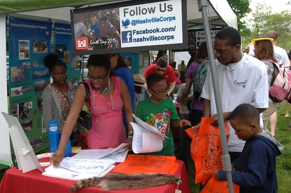 A family checks out the U.S. Army Corps of Engineers Nashville District booth April 18, 2015 during the Nashville Earth Day Festival at Centennial Park. They also collected water safety items and maps of local lakes that were available for free.
