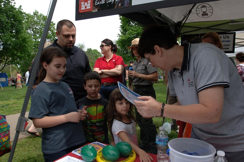Biologist Kim Franklin (Right) hands out water safety coloring pages to kids during the Nashville Earth Day Festival April 18, 2015 at Centennial Park.  The U.S. Army Corps of Engineers Nashville District's employees shared information with the public about environmental stewardship and water safety.