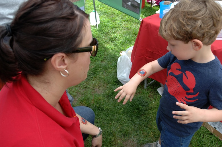 Biologist Mary Lewis helps a young boy put on a water safety tattoo at the U.S. Army Corps of Engineers Nashville District booth April 18, 2015 during the Nashville Earth Day Festival at Centennial Park.