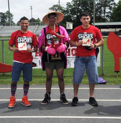 """First place winner, Cpl. Jose Colindres (center), second place winner HM2 Ricky Cuevas (left) and third place winner Sgt. Marcos Noyola show off their trophies. Men from all walks of life, including Marines and Sailors stationed at Marine Corps Logistics Base Albany, volunteered to support the """"Walk a Mile in Her Shoes"""" event benefitting Lily Pad, a local non-profit organization that supports victims of sexual assault and child abuse. The event was held April 18 at Deerfield-Windsor Upper Campus Track, Albany, Georgia."""