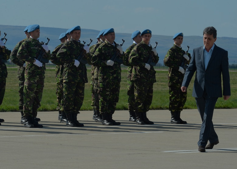 Mircea Dusa, Romanian Minister of National Defense, walks past a formation of Romanian air force Airmen during his arrival on the flightline at Campia Turzii, Romania, April 16, 2015. The minister attended a media event about the U.S. and Romanian air forces conducting Operation Atlantic Resolve which aims to strengthen interoperability and demonstrate the countries' shared commitment to the security and stability of Europe. (U.S. Air Force photo by Staff Sgt. Joe W. McFadden/Released)