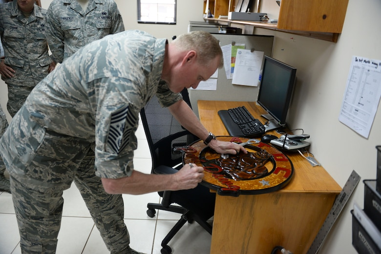 """Chief Master Sgt. James A. Cody autographs the """"Port Dawg"""" emblem of the air tactical operations center during a visit April 14, 2015, at Joint Task Force - Bravo, Soto Cano Air Base, Honduras. Cody visited multiple units on base during his time here, mentoring and engaging with Airmen from a senior leader perspective. (U.S. Air Force photo by Staff Sgt. Jessica Condit)"""