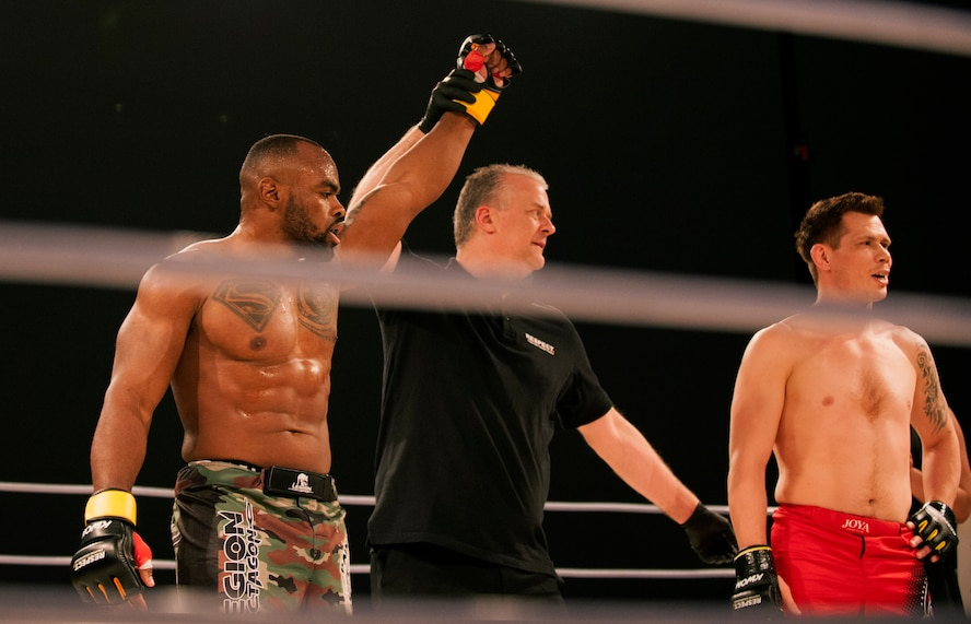 U.S. Air Force Tech. Sgt. Clinton Williams, 52nd Component Maintenance Squadron engine manager, left, raises his hand after he is pronounced the victor during the 12th Kwon Respect Fighting Championship in Wuppertal, Germany, April 11, 2015. The fight sealed William's second victory out of two fights in Germany and his 11th overall victory out of 12 fights in his mixed martial arts career. (U.S. Air Force photo by Airman 1st Class Timothy Kim/Released)