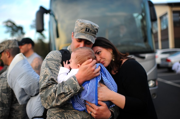 An Airman from the 606th Air Control Squadron meets his son for the first time at a deployment homecoming on Spangdahlem Air Base, Germany, April 17, 2015. The family surprised the Airman because he thought they would arrive in Germany the next day. (U.S. Air Force photo by Senior Airman Gustavo Castillo/Released)