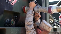 Private First Class Brenen Tischner, a motor transportation operator, with 1st Transport Support Battalion, Combat Logistics Regiment 1, 1st Marine Logistics Group, attaches a fuel hose to an AMK-23 Medium Tactical Vehicle Replacement during routine refueling maintenance on the outskirts of Marine Corps Air Station Yuma, Arizona, April 10, 2015. Tischner inspects vehicles like this each day to ensure optimum reliability for logistic units supporting the bi-annual, seven-week long Weapons Tactics and Instructor course at MCAS Yuma and the surrounding area. WTI, hosted by Marine Aviation Weapons and Tactics Squadron 1, provides advanced tactical training to certify Marine pilots as weapons and tactics instructors, preparing them to serve in key training officer billets in the fleet Marine force. (Marine Corps photo by Sgt. Cody Haas/Released)