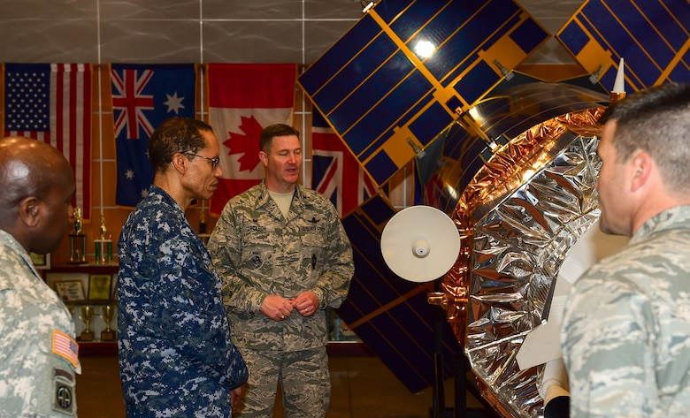 U.S. Navy Adm. Cecil D. Haney (second from left), U.S. Strategic Command commander, and U.S. Army Command Sgt. Maj. Patrick Z. Alston (left), USSTRATCOM senior enlisted leader, receive a mission brief from U.S. Air Force Col. Michael Jackson, 460th Operations Group commander, while viewing a Defense Satellite Program satellite model during their trip to Buckley Air Force Base, Colo., April 20, 2015. In addition to touring Buckley's missile warning facilities, Haney and Alston met with Airmen and Sailors from the base to discuss their role in supporting USSTRATCOM's global strategic missions. USSTRATCOM is one of nine DoD unified combatant commands and is charged with strategic deterrence; space operations; cyberspace operations; joint electronic warfare; global strike; missile defense; intelligence, surveillance and reconnaissance; combating weapons of mass destruction; and analysis and targeting. (U.S. Air Force photo by Amn. 1st Class Luke W. Nowakowski)