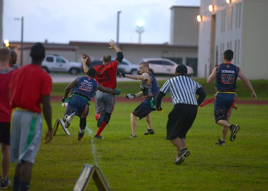 A 36th Security Forces Squadron member attempts to pull a flag from a 664th Combat Communications member as he tip-toes along the sideline during the flag football championship, April 20, 2015. The 36th SFS defeated the 664th CBCS 14-0 in the championship. (U.S. Air Force photo by Airman 1st Class Joshua Smoot/Released)