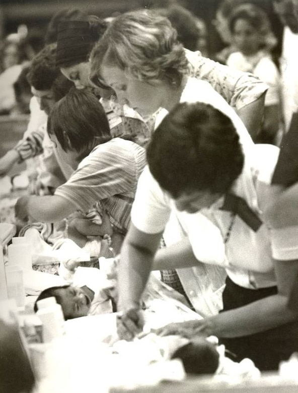 During Operation Baby Lift long lines of volunteers tend to the babies.  The babies were bathed, clothed, fed, provided medical care if needed, and simply comforted during their layover at either the Honolulu International Airport or MAC Terminal on Hickam Air Force Base. Operation Baby Lift ran from April 3-26, 1975 and evacuated more than 3,000 babies and young children, most of whom were orphans, to the U.S. (U.S. photo provided by 15 WG historian office)