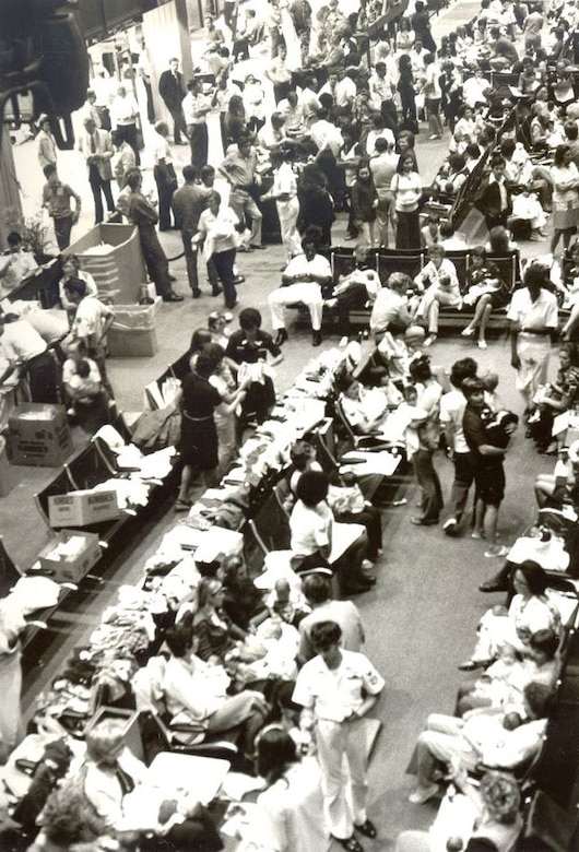 """On 5 April 1975, the first plane full of Operation Baby Lift babies arrived at the Honolulu International Airport.  That night """"temporary mothers and fathers"""" took care of the over 400 babies at in the airports holding area set up by Customs and Immigrations Officials until the aircraft departed the next morning.(U.S. Air Force photo provided by 15 WG historian office)"""
