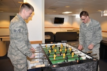 Senior Airman Kenneth Blount, 354th Force Support Squadron and Airman 1st Class Jonathan Coffey, 354th Communications Squadron, play a game of foosball on a new table in their dormitory's common room. Dormitory residents are able to enjoy approximately $30,000 in quality of life upgrades to the common rooms of dormitory buildings. (U.S. Air Force photo by Staff Sgt. Kirsten Wicker/Released)