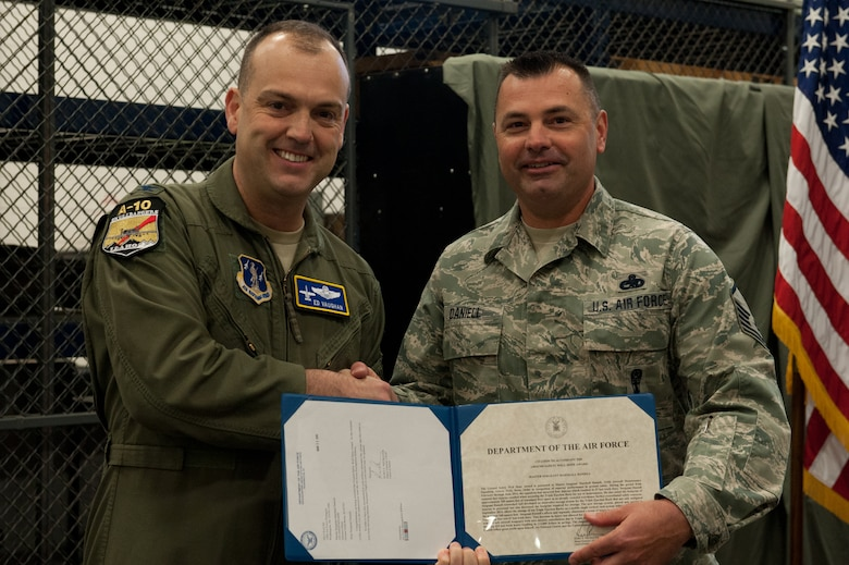 Master Sgt. Marshall J. Daniell, an armament systems specialist with the 124th Aircraft Maintenance Squadron Weapons Load Shop, is presented with an Air Force Ground Safety Well Done award from Col. Edward Vaughan, the director of safety for the Air National Guard, for researching and developing a storage system for the squadron???s Triple Ejection Racks April 12, 2015, at Gowen Field, Boise, Idaho. The TERs rack was previously stored on shelving units and is now stored on a mobile platform that can hold up to 10 racks. (Air National Guard photo by Tech. Sgt. Joshua Allmaras/Released)
