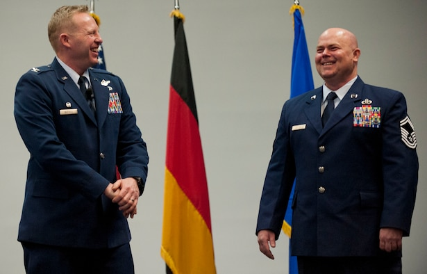 U.S. Air Force Col. Joe McFall, 52nd Fighter Wing commander, left, looks on as U.S. Air Force Senior Master Sgt. Christopher Collins, 52nd Civil Engineer Squadron facilities systems superintendent, right, speaks during the  52nd Mission Support Group commander's call at the Skelton Memorial Fitness Center in Spangdahlem Air Base, Germany, April 16, 2015. McFall presented two medals to Collins for his actions during a deployment to Afghanistan in 2013. (U.S. Air Force photo by Airman 1st Class Timothy Kim/Released)