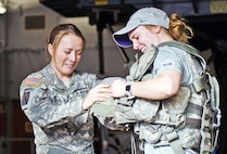 Staff Sgt. Sarah Snider (left), 2nd GSAB, 1st Avn. Regt., 1st CAB, 1st Inf. Div., shows Kansas State University volleyball player Sheridan Zarda equipment she wears as a flight engineer aboard a CH-47 Chinook helicopter March 9 at Fort Riley, Kansas. Zarda and her teammates also talked to female Soldiers from the 1st CAB about experience as Soldiers and daily life.