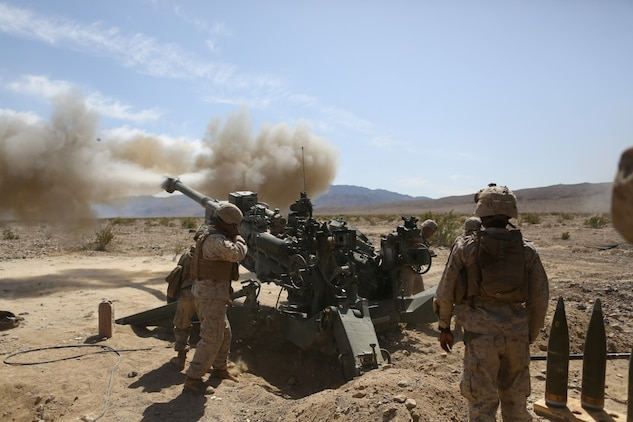 Corporal Osmar S. Gorish, a section chief for Battery A, 1st Battalion, 11th Marine Regiment, 1st Marine Division, observes a round being shot down range during Exercise Desert Scimitar 2015 aboard Marine Corps Air Ground Combat Center Twentynine Palms, Calif., April 20, 2015. The tough, realistic live-fire training central to Desert Scimitar allows Division units to train in order to maintain readiness and meet current and real-world operational demands.