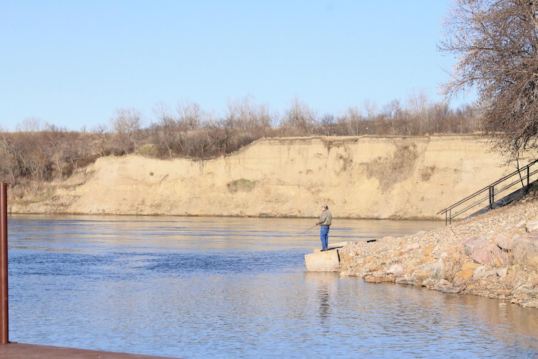 A visitor fishes from the shore near the downstream boat ramp at the Garrison Dam near Riverdale, North Dakota
