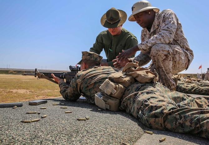 Corporal Hector F. Deleon (left), primary marksmanship instructor, and Cpl. Tony Williams, range coach, Range Company, Weapons and Field Training Battalion, assist a recruit of Kilo Company, 3rd Recruit Training Battalion, in improving his next shot during rifle week at Edson Range, Marine Corps Base Calif., April 14. The PMIs spend every day for two weeks with the recruits making sure they are comfortable with their weapons and understand the fundamentals of marksmanship. Today, all male recruits recruited from recruiting stations west of the Mississippi are trained at MCRD San Diego. The depot is responsible for training more than 16,000 recruits annually. Company K is scheduled to graduate from recruit training on May 29.