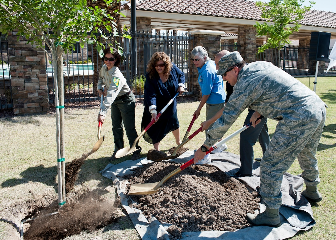 Lt. Col. Brian Hartless (far right), 99th Civil Engineer Squadron commander, joins distinguished guests at the Earth and Arbor Day 2015 celebration in planting a new tree at Nellis Air Force Base, Nev., April 20, 2015. Nellis AFB is acknowledged annually by the National Arbor Day Foundation for its continual dedication to planting new trees. In 1872, the State Board of Agriculture adopted J. Sterling Morton's resolution establishing Arbor Day as a special day for planting trees. (U.S. Air Force photo by Airman 1st Class Jake Carter)