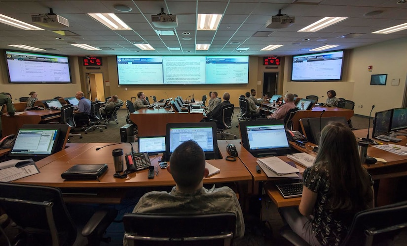 Squadron Airmen and civilians man the Emergency Operations Center April 21, 2015, at Joint Base Charleston, S.C., during a Hurricane Exercise. The EOC is a centralized command and control facility responsible for providing strategic decisions during disasters or emergencies. (U.S. Air Force illustration/Senior Airman Jared Trimarchi)